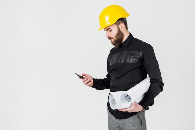 Ein männlicher architekt, der den gelben hardhat betrachtet smartphone trägt
