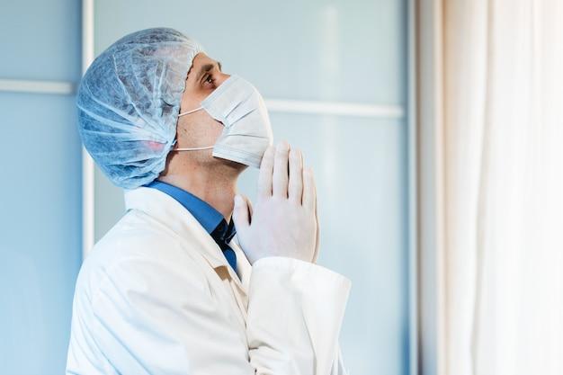 Ein männlicher arzt betet ins krankenhaus für das leben des patienten und das ende der coronavirus-pandemie.