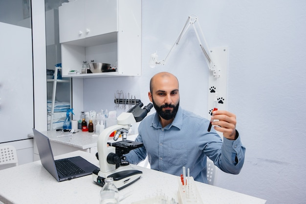 Ein männlicher arzt im labor untersucht viren und bakterien unter dem mikroskop. erforschung gefährlicher viren und bakterien.