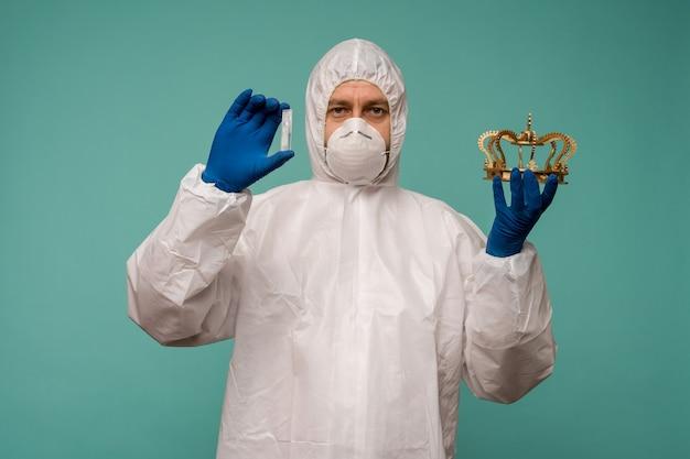 Ein männlicher arzt in schutzoverall und maske hält eine ampulle mit einem impfstoff und einer krone in den händen. coronovirus-schutzkonzept in china.