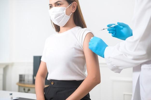 Ein männlicher arzt injiziert den covid-19-impfstoff in den patientenarm, die covid-19-impfung und das gesundheitskonzept
