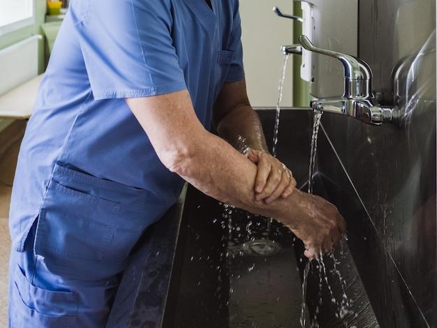 Ein männlicher arzt wäscht seine hände gründlich mit seife unter fließendem wasser in einer edelstahlspüle. notwendige desinfektionsmaßnahmen.
