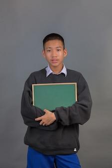 Ein männlicher asiatischer student, der eine schwarze strickjacke umarmt das grüne brett und steht auf einem grau trägt.