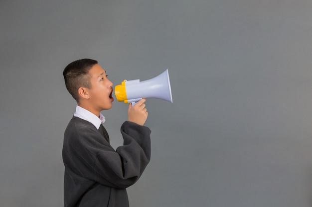 Ein männlicher asiatischer student, der eine schwarze strickjacke unter verwendung eines megaphons trägt und auf einem grau steht.