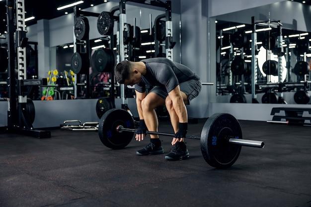 Ein männlicher athlet, der sich auf ein langhantel-fitness-training im modernen fitnessstudio vorbereitet
