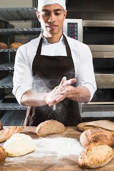Ein männlicher bäcker, der das mehl mit den händen auf geknetetem teig abwischt