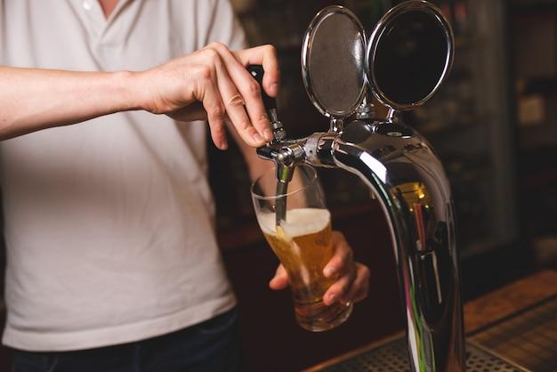 Ein männlicher barmann gießt ein glas bier aus dem wasserhahn