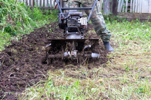 Ein männlicher bauer pflügt den boden mit einem handgeführten benzintraktor, der sich darauf vorbereitet, samen am frühlingstag aus der nähe zu pflanzen