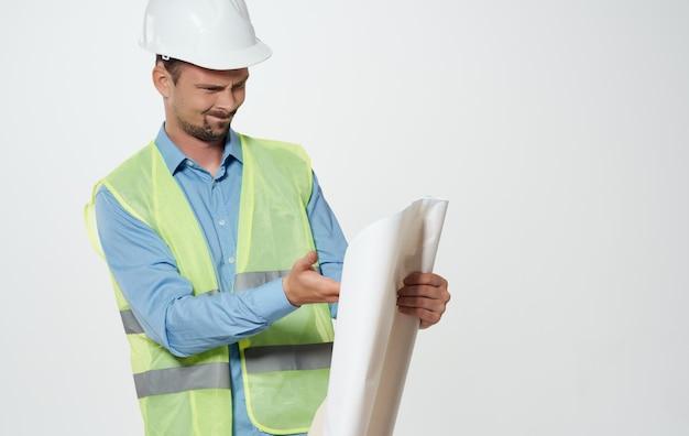 Ein männlicher bauingenieur mit einer papierrolle in den händen und einem weißen schutzhelm auf dem kopf.
