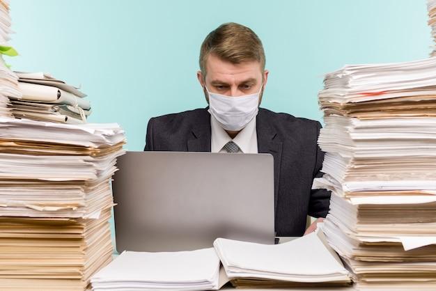 Ein männlicher buchhalter oder unternehmensleiter arbeitet in einem büro in einer pandemie angesichts der angesammelten papierarbeit. - ich
