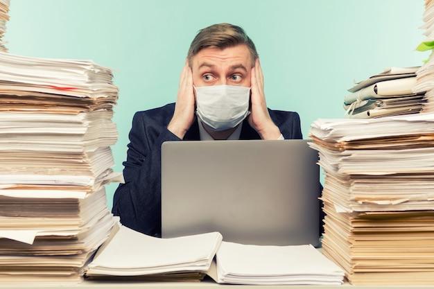 Ein männlicher buchhalter oder unternehmensleiter arbeitet in einem büro in einer pandemie angesichts der angesammelten papierarbeit.