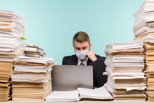 Ein männlicher buchhalter oder unternehmensleiter schläft in einem büro in einer pandemie angesichts der angesammelten papierarbeit.