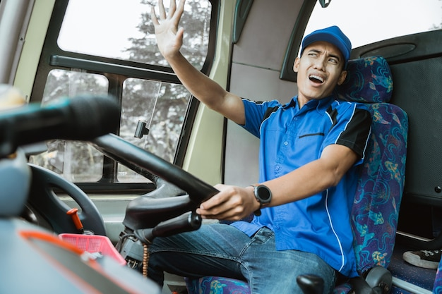 Ein männlicher busfahrer in blauer uniform mit einem krachenden ausdruck während der fahrt des busses