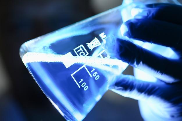 Ein männlicher chemiker hält ein reagenzglas aus glas in der hand und läuft über eine flüssigkeit
