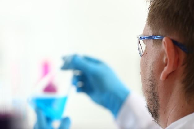 Ein männlicher chemiker hält ein reagenzglas aus glas in seinen handüberläufen