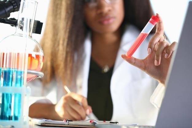 Ein männlicher chemiker hält ein reagenzglas aus glas