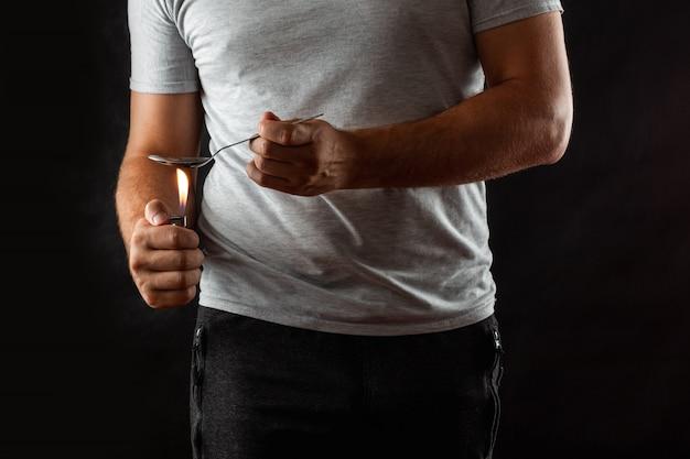 Ein männlicher drogenabhängiger bereitet drogen in einem löffel mit einem feuerzeug vor