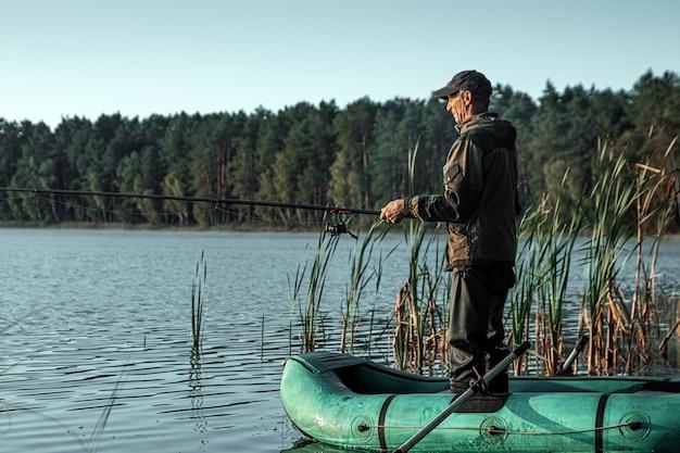 Ein männlicher fischer auf dem see steht im wasser und fischt nach einer angelrute