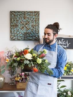 Ein männlicher florist, der blumendekoration in seinem shop betrachtet