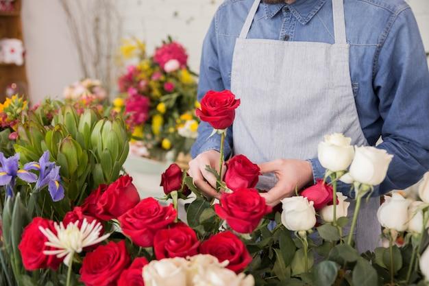 Ein männlicher florist, der die frischen rosen im blumengeschäft arrangiert