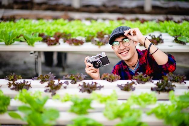 Ein männlicher fotograf fotografiert in seinem salatgarten und genießt das fotografieren.