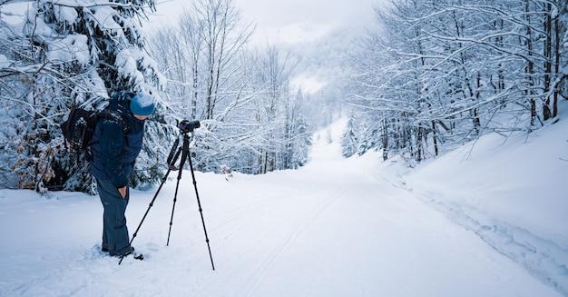 Ein männlicher fotograf stellt seine kamera auf einem stativ ein