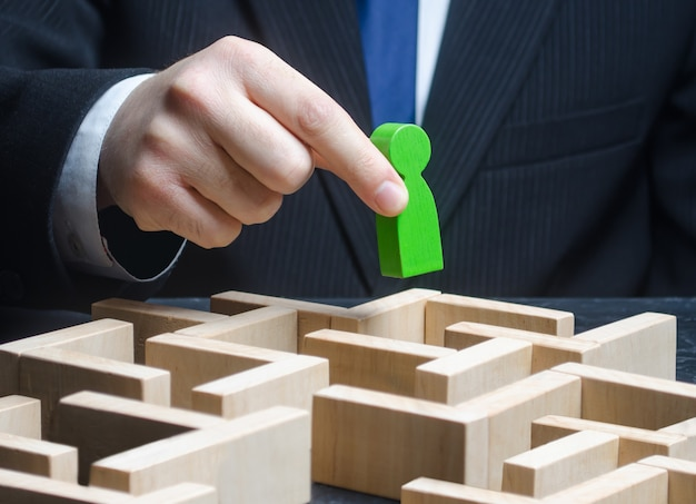 Ein männlicher geschäftsmann hält eine grüne figur über einem labyrinth.