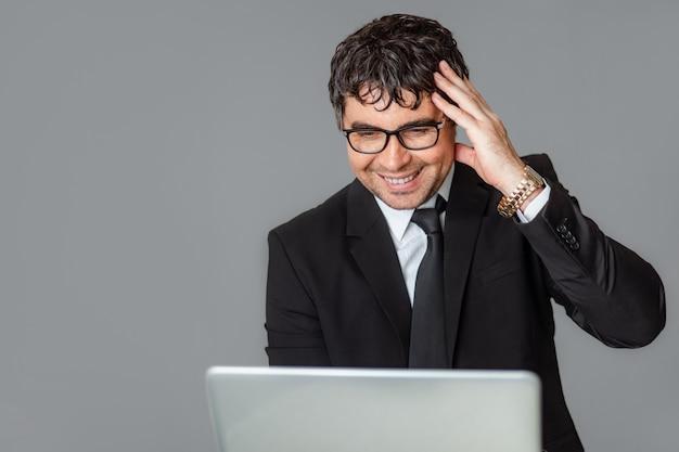 Ein männlicher geschäftsmann in einem schwarzen anzug und einer brille mit einem laptop.