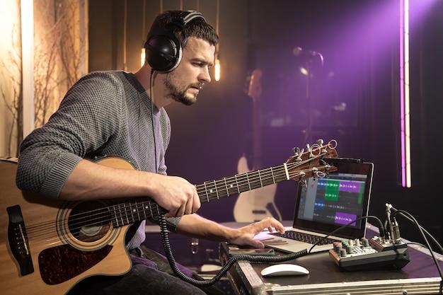 Ein männlicher gitarrist mit kopfhörern, die während der tonaufnahme an einen tonmischer angeschlossen sind, arbeitet mit einem laptop in einem aufnahmeprogramm.