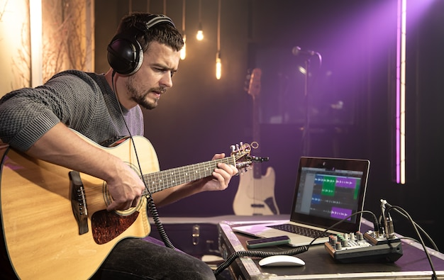 Ein männlicher gitarrist spielt gitarre mit kopfhörern, die an einen soundmixer angeschlossen sind. digitale wellenform auf laptop-monitor.