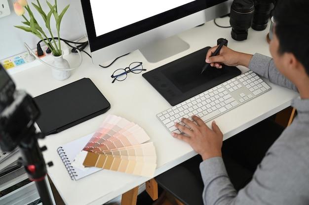 Ein männlicher grafikdesigner, der mit tablette am arbeitsplatz arbeitet.