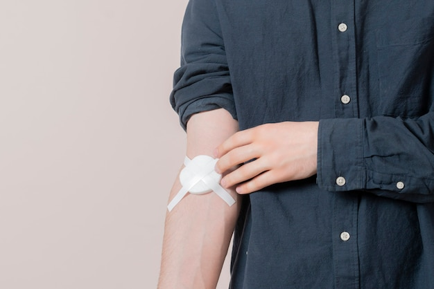 Ein männlicher handverband nach der blutspende, medizinischer patientenspender, der gegen den wandkopierraum steht