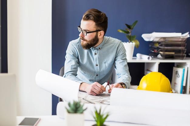 Ein männlicher ingenieur, der am arbeitsplatz mit architekturplan auf tabelle sitzt