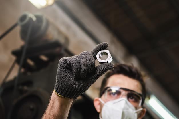 Ein männlicher ingenieur überprüft die qualität des metallteils anhand der metallarbeiten in der fabrik. die herstellung von metallteilen und die überprüfung der qualität.