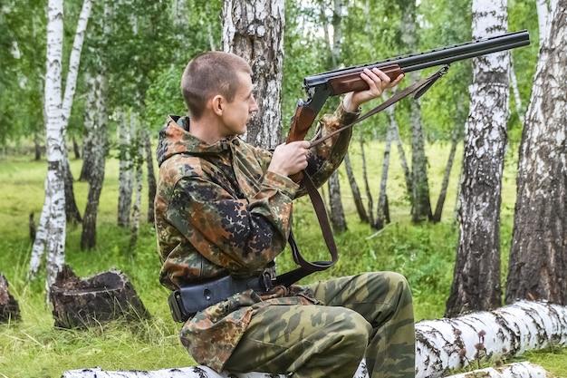 Ein männlicher jäger sitzt auf einem baumstamm und überprüft sein gewehr vor der jagd