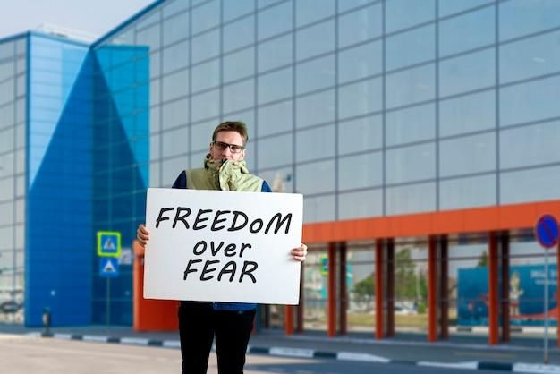 Ein männlicher junger aktivist mit pappe, soloprotest, politischer geste, der ein plakat zeigt