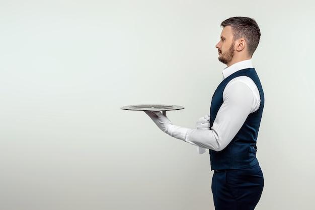 Ein männlicher kellner im weißen hemd steht seitlich mit einem silbernen tablett. das konzept des servicepersonals, das kunden in einem restaurant bedient.