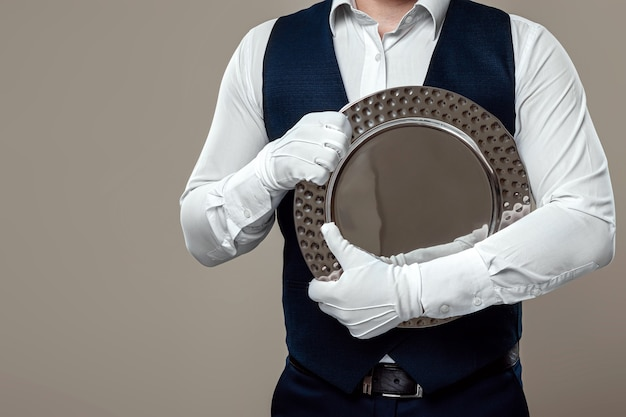 Ein männlicher kellner in weißem hemd und weißen handschuhen, der mit einem silbernen tablett steht, drückt es an seine brust. das konzept des servicepersonals, das kunden in einem restaurant bedient.