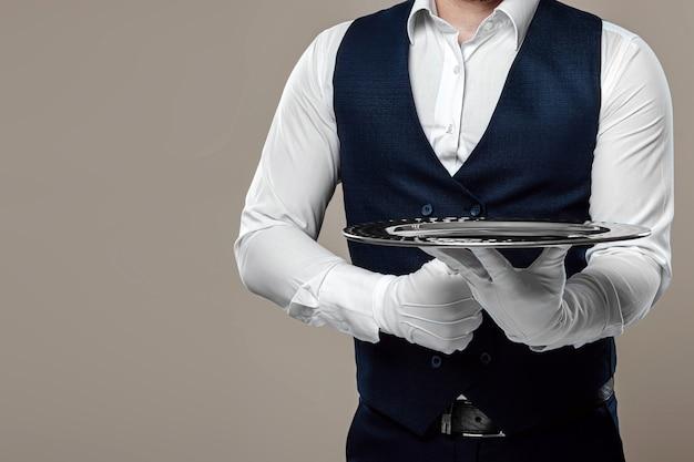 Ein männlicher kellner in weißem hemd und weißen handschuhen steht mit einem silbernen tablett. das konzept des servicepersonals, das kunden in einem restaurant bedient.
