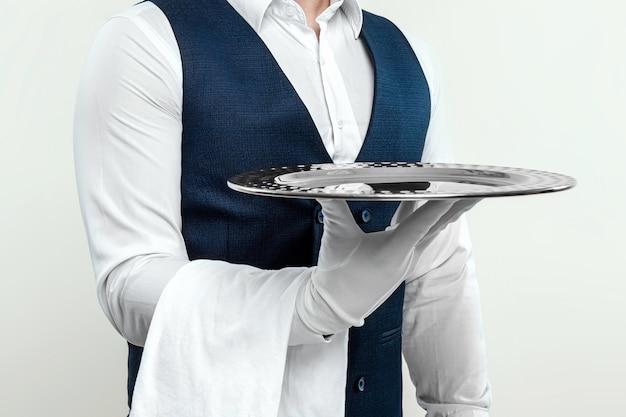 Ein männlicher kellner in weißem hemd und weißen handschuhen steht seitlich mit einem silbernen tablett. das konzept des servicepersonals, das kunden in einem restaurant bedient.