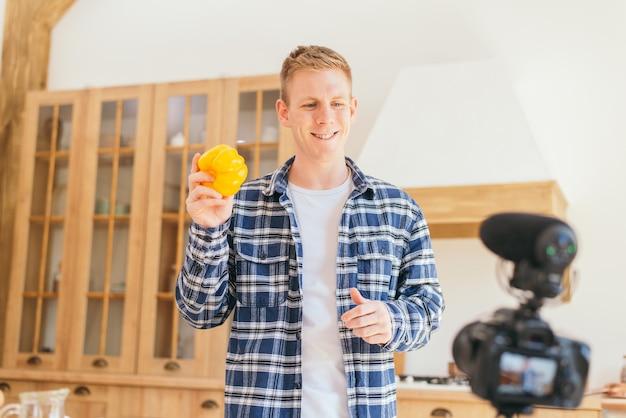 Ein männlicher koch hält eine gelbe paprika in den händen und schafft inhalte in die kamera einfluss der gesellschaft