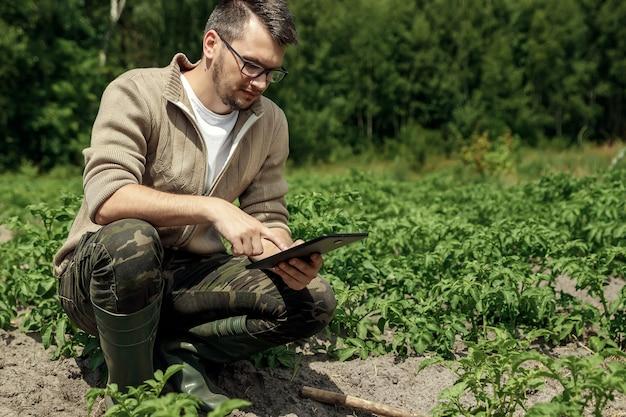 Ein männlicher landwirt, der auf dem gebiet sitzt und eine tablette verwendet