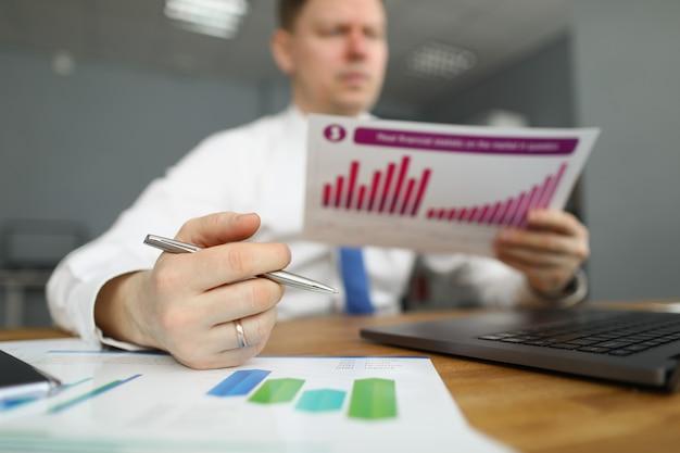 Ein männlicher manager im hemd sitzt an einem tisch und hält einen finanzbericht mit diagramm