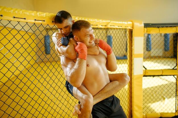 Ein männlicher mma-kämpfer führt seinem gegner in einem käfig im fitnessstudio einen schmerzhaften choke-hold durch.