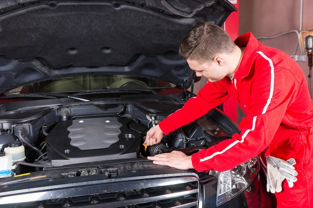 Ein männlicher motormechaniker wird den ölstand in einem automotor prüfen