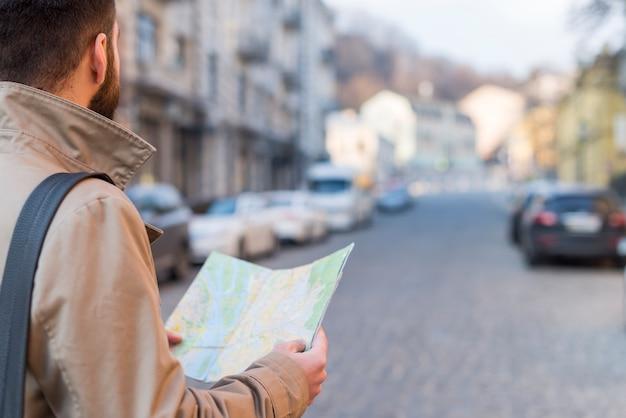 Ein männlicher reisender, der in der hand die karte findet den weg auf stadtstraße hält