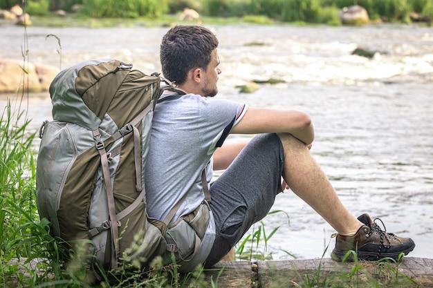 Ein männlicher reisender mit einem großen wanderrucksack ruht sich in der nähe des flusses aus.