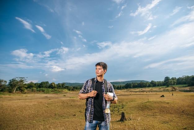Ein männlicher reisender mit einem rucksack, der eine karte trägt und auf der wiese steht.