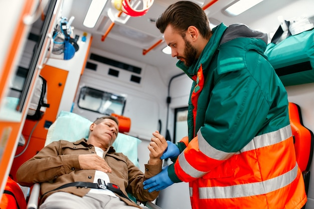 Ein männlicher sanitäter in uniform misst den puls eines älteren patienten, der in einem modernen krankenwagen auf einer trage liegt.