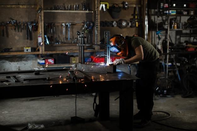 Ein männlicher schweißer in einem schutzhelm arbeitet in seiner werkstatt.